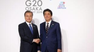 Le président sud-coréen Moon Jae-in (g) et le Premier ministre japonais Shinzo Abe lors du sommet du G20, le 28 juin 2019 à Osaka
