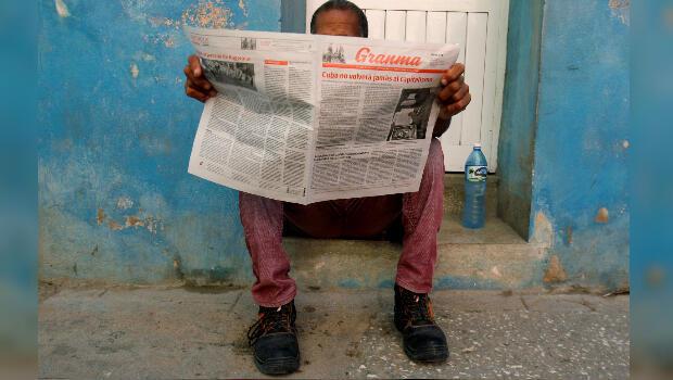 """Imagen de archivo. Un hombre lee el periódico Granma. En la portada se lee """"El capitalismo nunca volverá a Cuba"""". La Habana, Cuba, el 21 de julio de 2018."""