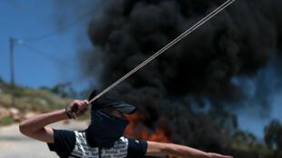 فلسطيني يرشق قوات إسرائيلية بحجارة قرب إطارات مشتعلة في بلدة كفر قدوم في الضفة الغربية المحتلة في الثامن من أيار/مايو 2020