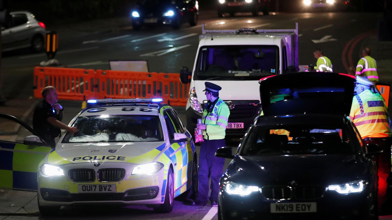 Los oficiales de policía y sus vehículos son vistos en un cordón en la escena de múltiples apuñalamientos reportados en Reading, Reino Unido, el 20 de junio de 2020.
