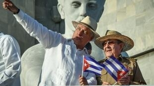 Cuban President Miguel Diaz-Canel (with his arm raised) stands next to Raul Castro, first secretary of the island's Communist Party, on May 1, 2019 in Havana; a new law will bring governmental change without touching the central role of the party