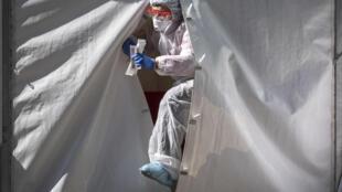 أحد أفراد طاقم طبي يخرج من خيمة مخصصة لفحوص الإصابة بكوفيد-19 في وسط موسكو، 2 أيار/مايو 2020