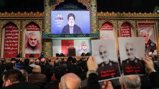 Supporters of Shiite Hezbollah movement hold posters of slain Iranian Major General Qasem Soleimani as the movement's leader Hasan Nasrallah delivers a speech on a screen, in the Lebanese capital Beirut's southern suburbs on January 5, 2020.