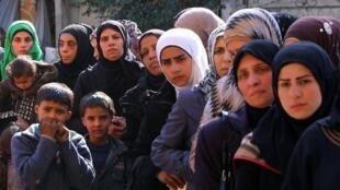 لاجئون فلسطينيون ينتظرون حصصا غذائية توزعها وكالة انروا في مخيم اليرموك في 10 آذار/مارس 2015