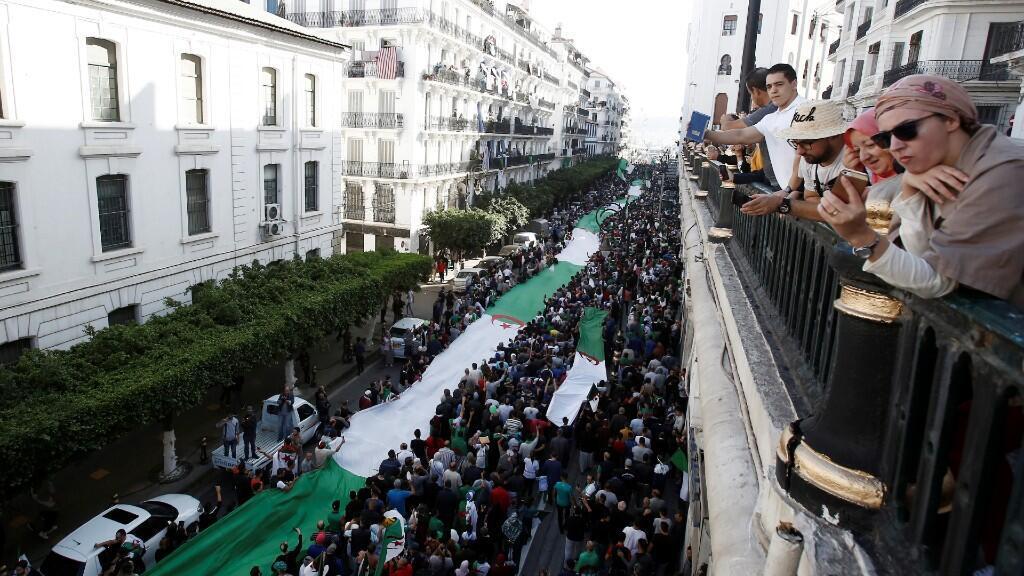 Cientos de manifestantes portan una gran andera de Argelia durante el 65 viernes consecutivo de protestas, en Argel, 1 de noviembre de 2019.