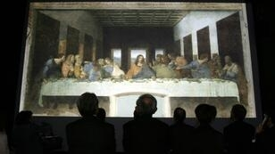 "Guests look at a life-sized projected image of ""The Last Supper"" at a digital exhibition in Tokyo on 26 April 2006"