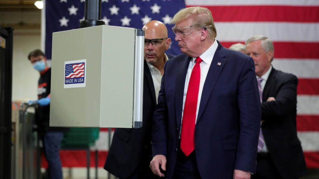 El presidente de los Estados Unidos, Donald Trump, observa una máquina de fabricación de máscaras protectoras que le muestra el vicepresidente de cadena de suministro integrada de Tonywell, Tony Stallings, durante un recorrido por las instalaciones de fabricación de máscaras de Honeywell. En Phoenix, Arizona, Estados Unidos, 5 de mayo de 2020.