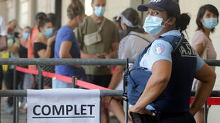"A French municipal police employee stands near a fence with a sign reading ""full"" as people queue at a testing site for coronavirus disease in Nice, France, August 24, 2020."
