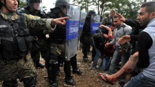 Des migrants blessés, face aux policiers macédoniens à la frontière avec la Grèce, le 21 août 2015.