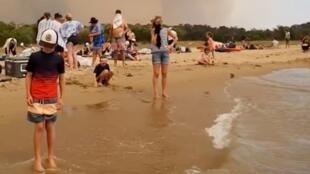 Des personnes fuient les incendies sur la plage de Batemans Bay en Australie, le 31 décembre 2019.