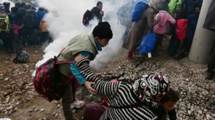 Une femme tombe, alors que la police macédonienne utilise des gaz lacrymogènes contre des centaines de migrants à la frontière gréco-macédonienne, le 29 février 2016.