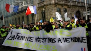 """Los manifestantes que usan chalecos amarillos participan en una manifestación del movimiento de 'chalecos amarillos' en Marsella, Francia, el 5 de enero de 2019. El texto del cartel dice: """"Francia no está en venta""""."""