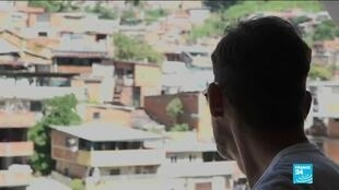 Venezuelan Richard Martinez looks through the window of his Caracas home. HIV-positive, Martinez tells FRANCE 24 his anti-retroviral drugs have become harder and harder to get.