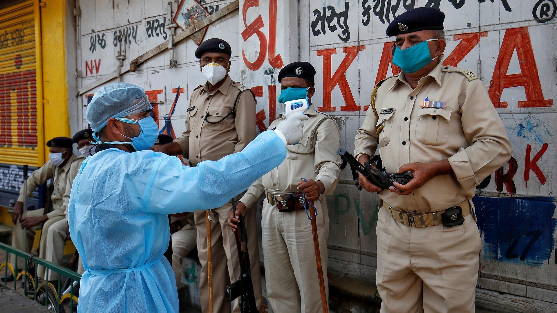 رجل إسعاف يقيس درجة حرارة رجال شرطة بمدينة أحمد آباد الهندية خلال إجراءات العزل المفروضة على البلاد، 9 أبريل/نيسان 2020.