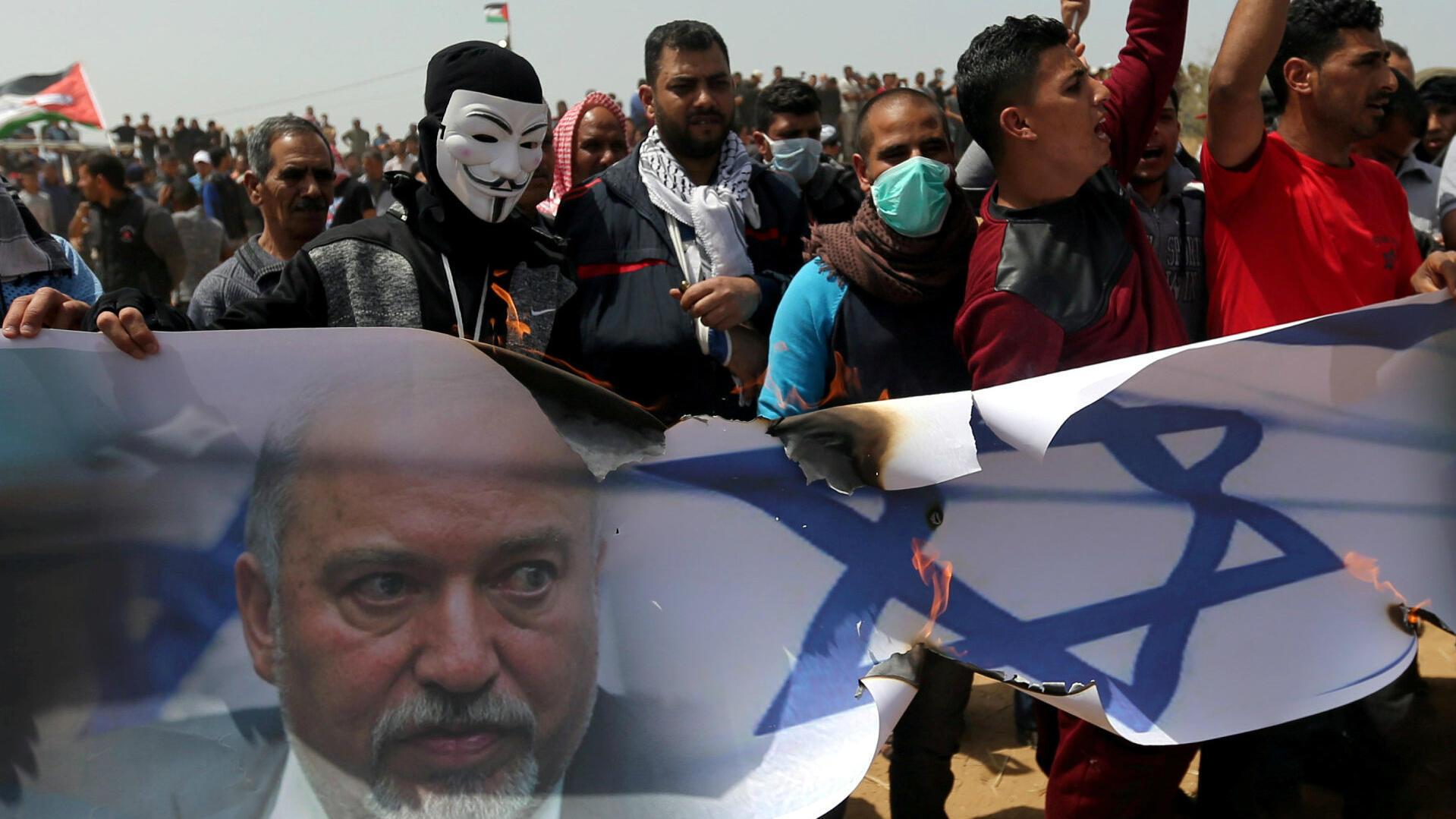 Manifestantes palestinos quemando una pancarta representando una bandera israelí con una foto del exministro de Defensa, Avigdor Lieberman, durante una protesta en el sur de la Franja de Gaza, el 13 de abril de 2018.