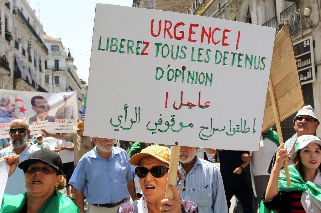 """Une manifestante brandit une pancarte réclamant la libération des """"détenus d'opinion"""", lors d'une manifestation dans la capitale Alger, le 12 juillet 2019."""