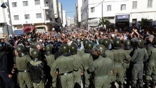 متظاهرون يهتفون أمام قوات الأمن المغربية خلال مسيرة تتحدى المنع الذي فرضته السلطات في مدينة الحسيمة المغربية، 20 تموز/يوليو 2017