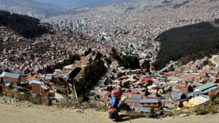Una mujer indígena que carga un bebé camina en una zona de bajos ingresos en El Alto, La Paz, Bolivia, el 22 de mayo de 2020, en medio de la pandemia del nuevo coronavirus.