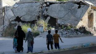 En una imagen de archivo, una familia mira un edificio derrumbado en la ciudad de Idlib, Siria, el 27 de mayo de 2019.