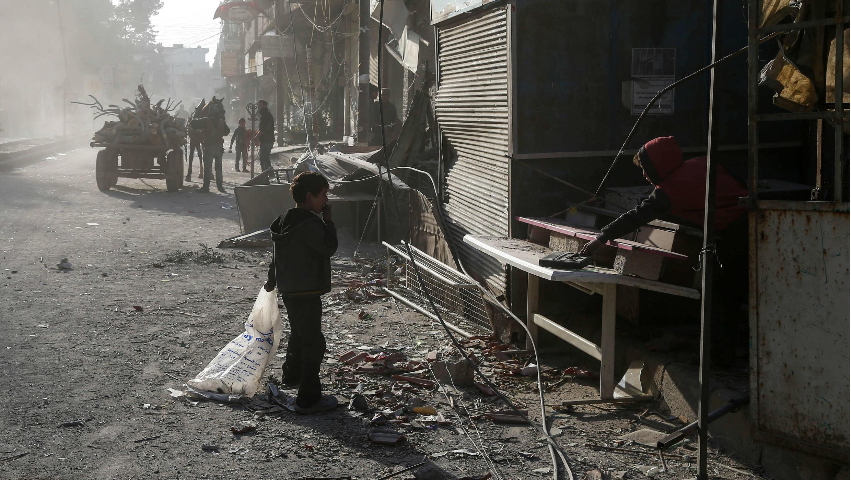 Niños sirios limpian su tienda de escombros después de los informes de ataques aéreos del régimen en la ciudad de Kafr Batna