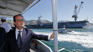 French President François Hollande pictured near the aircraft carrier Charles de Gaulle during a visit to the naval base in Toulon on July 27.