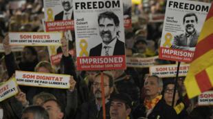 Manifestantes a favor de la independencia de Cataluña sostienen unas pancartas que pide la liberación de los líderes separatistas catalanes encarcelados Jordi Sánchez y Jordi Cuixart, el 16 de enero de 2018.