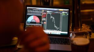Un opérateur de Bourse à Hong Kong observe la chute de la livre sterling