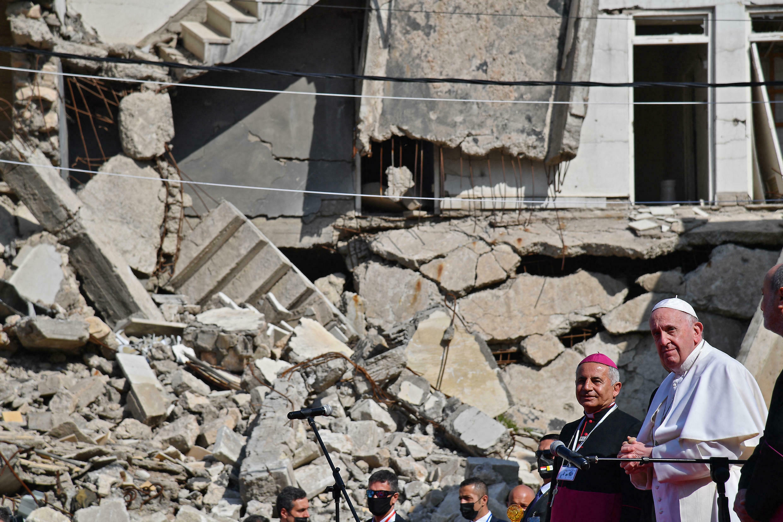 El papa Francisco, acompañado por el arzobispo católico caldeo de Mosul, Najib Michaeel Moussa, observa las ruinas de la iglesia católica siria de la Inmaculada Concepción, en la ciudad norteña de Mosul, el 7 de marzo de 2021.