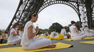 Parisians attend a yoga session under the Eiffel Tower on June 21, 2015, to mark the first International Yoga Day.