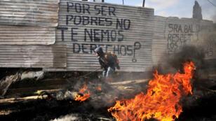 Fotografía de archivo fechada el 30 de julio de 2014 que muestra a un joven mientras participa en una protesta por un desalojo en el asentamiento Linda Vista de Ciudad de Guatemala (Guatemala).
