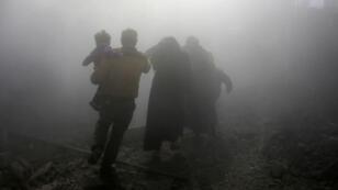 Una familia siria atraviesa una nube de polvo. Huye de los ataques aéreos del régimen en la ciudad de Jisreen, en la sitiada región de Guta oriental, en las afueras de la capital, Damasco, el 8 de febrero de 2018. En el cuarto día consecutivo de los fuertes bombardeos del régimen de Bashar Al Assad en el enclave de los rebeldes de Guta Oriental, cerca de Damasco. 8 de febrero.