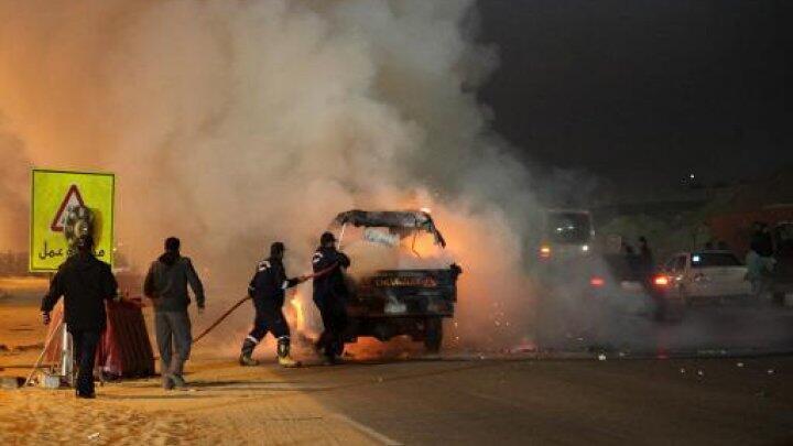 رجال الإطفاء يحاولون إخماد النار المشتعلة في سيارة أمام استاد رياضي في القاهرة في 8 شباط/فبراير 2015