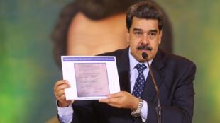 Le président du Venezuela, Nicolas Maduro, montrant le contrat signé par un conseiller de l'opposition sur une invasion de son pays.