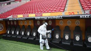 عامل في بلدية اسطنبول التركية يقوم بإجراءات تعقيم ملعب لكرة القدم، في 14 آذار/مارس 2020.
