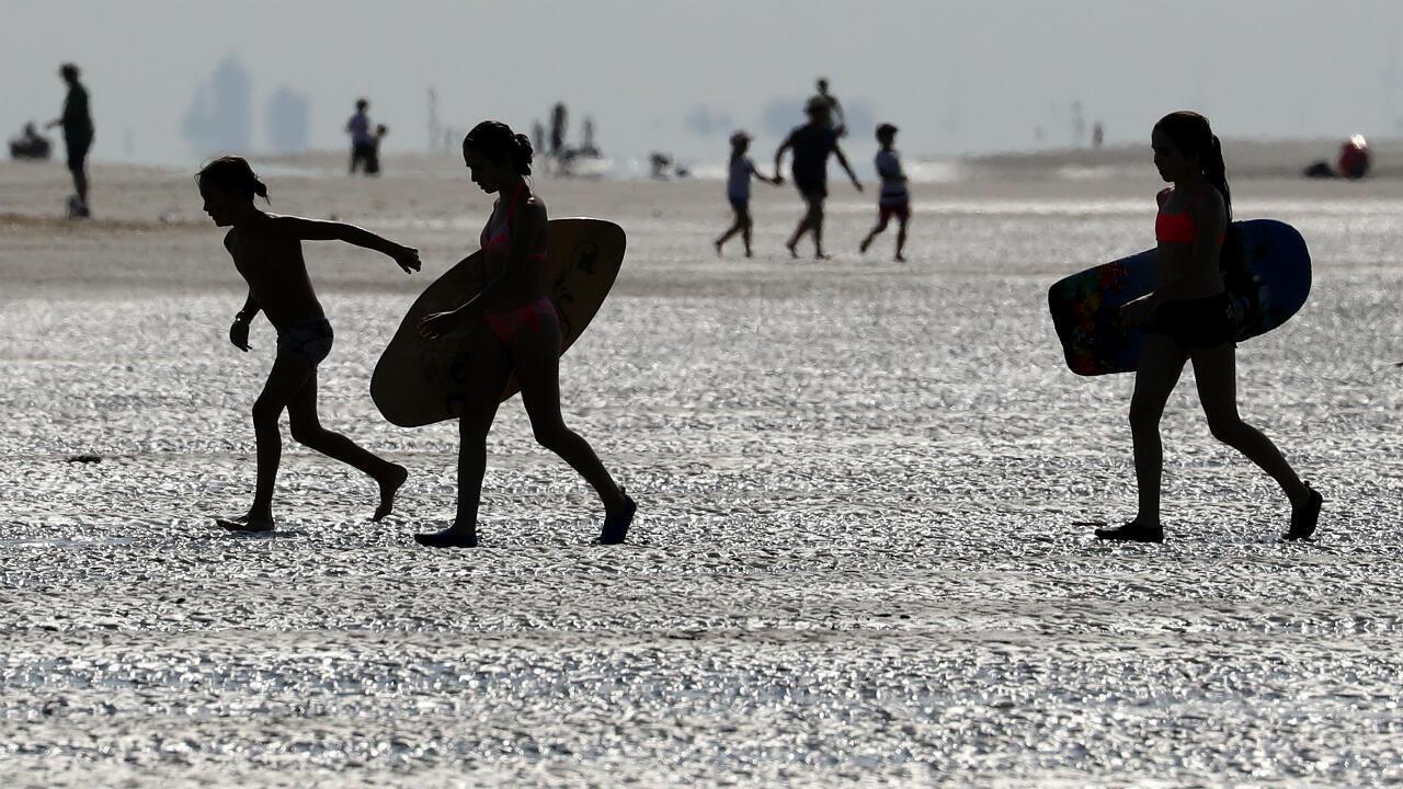 Jóvenes caminan por la playa durante un caluroso día de verano en Oostduinkerke, Bélgica, el 29 de julio de 2019.