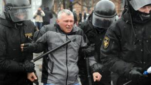 Des policiers maintiennent un manifestant pendant un rassemblement à Minsk, le 25 mars 2017.