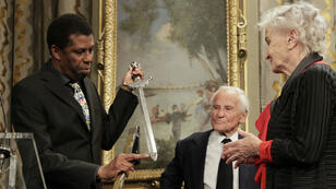 Haitian Canadian writer Dany Laferrière (L) receives his academician sword from French novelist and French Academy member Jean d'Ormesson (C) at City Hall in Paris on May 26, 2015.