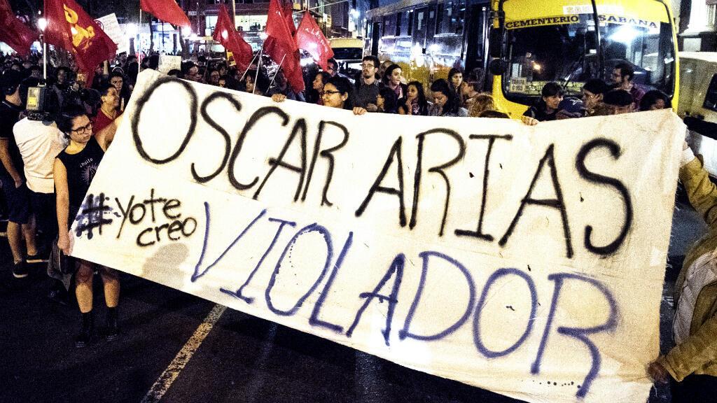 """Con un cartel que dice """"Óscar Arias violador"""", las personas protestan contra el Premio Nobel de la Paz y expresidente de Costa Rica Óscar Arias, acusado de agresión sexual por al menos 9 mujeres. La marcha tuvo luga en San José, Costa Rica, el 8 de febrero de 2019."""