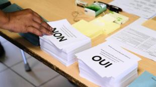 Une personne prend les bulletins avant de voter au référendum sur l'indépendance de la Nouvelle-Calédonie, le 4 octobre 2020 dans un bureau à Nouméa
