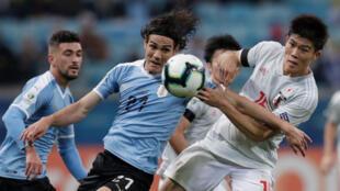 Edinson Cavani y Takehiro Tomiyasu pelean por el balón durante el partido Uruguay-Japón en Porto Alegre, Brasil, el 20 de junio de 2019.