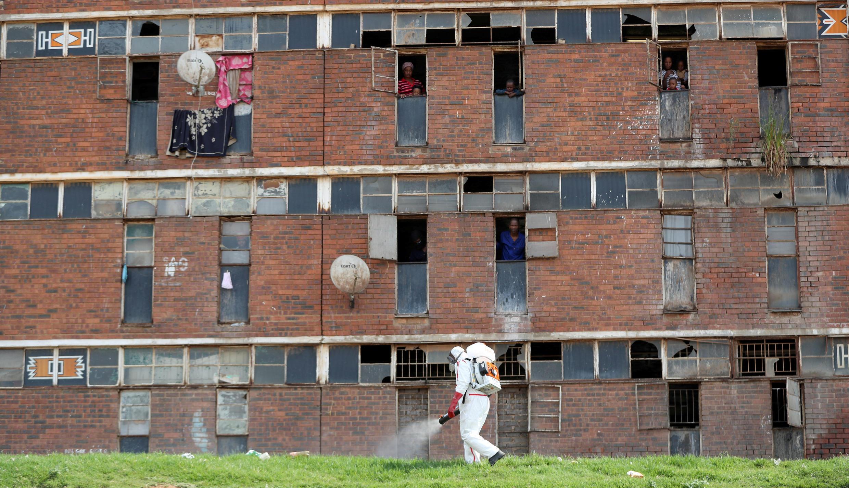 Un homme portant une combinaison de protection diffuse du désinfectant dans un quartier pauvre d'Alexandra en Afrique du Sud.