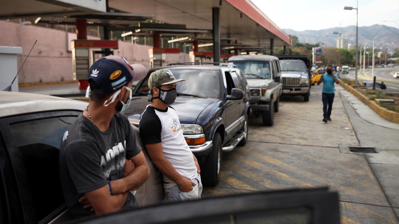 Varios usuarios de una estación de gasolina, con máscaras protectoras, se paran junto a los vehículos en fila durante la cuarentena a nivel nacional en respuesta a la propagación de la enfermedad por coronavirus en Caracas, Venezuela, el 30 de marzo de 2020.
