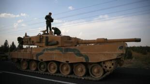 Des soldats turcs se tiennent debout sur un tank sur une route proche de la frontière turco-syrienne près de Ceylanpinar, le 18octobre2019.