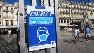 """Des personnes portant un masque marchent à côté d'un panneau d'affichage portant l'inscription """"Masque obligatoire dans le centre-ville de Montpellier"""", le 25 août 2020, à Montpellier, dans le sud de la France."""