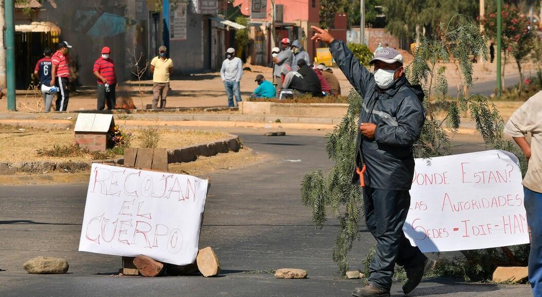 Vecinos protestan por la presencia del cuerpo sin vida de un hombre que permaneció durante horas abandonado en una calle, en Cochabamba, Bolivia, el 5 de julio de 2020.