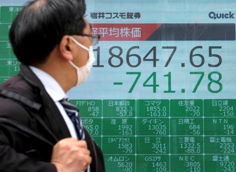 Un peatón pasa junto a un tablero de cotizaciones que muestra la cotización de la Bolsa de Valores de Tokio, el 30 de marzo de 2020.