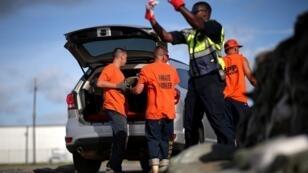 Los reclusos del sistema de la Prisión Parroquial de St. Bernard mientras cargan bolsas de arena en los automóviles de los residentes ante el paso de la tormenta Barry en Luisiana, Estados Unidos, el 11 de julio de 2019.