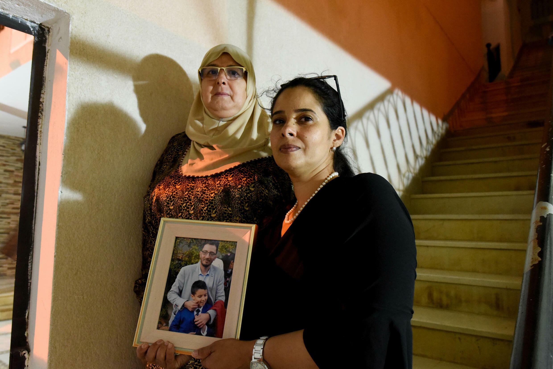 L'épouse et la mère du député Yassine Ayari posent avec une photo de ce dernier, sur les lieux où il a été arrêté le 30 juillet dernier, quelques jours après le gel du Parlement et la levée de son immunité parlementaire.