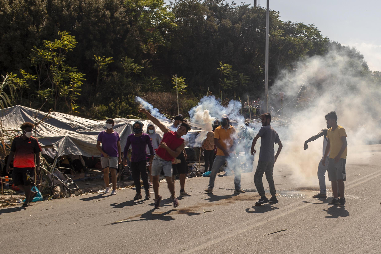 مهاجرون يرمون القنابل المسيلة للدموع التي أطلقتها شرطة مكافحة الشغب اليونانية لتفريقهم خلال مظاهرة احتجاجا على سلسلة حرائق شهدها مخيم موريا بجزيرة ليسبوس