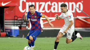 نجم برشلونة الدولي الارجنتيني ليونيل ميسي يحاول تخطي زميله السابق في النادي الكاتالوني مهاجم اشبيلية منير الحدادي في مباراة الفريقين في الدوري الاسباني في 19 حزيران/يونيو 2020.